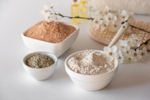 Tigela de cerâmica com pó de argila vermelha, ingredientes para a máscara facial e corporal caseira ou esfoliação e raminho fresco de cerejeira. conceito de spa e cuidados com o corpo.