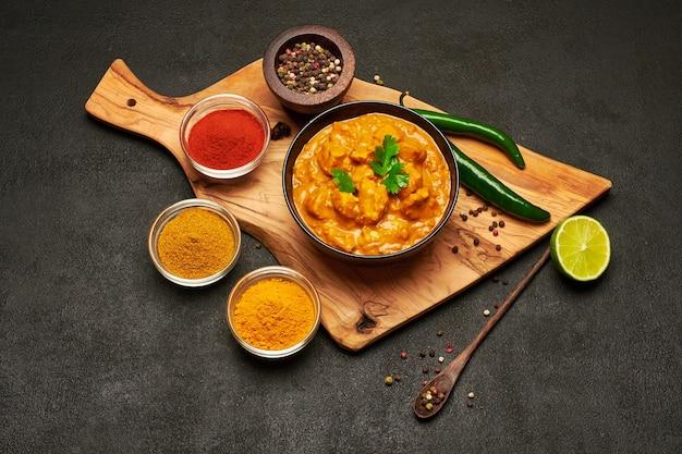Tigela de cerâmica preta com curry de frango tradicional e especiarias na mesa escura