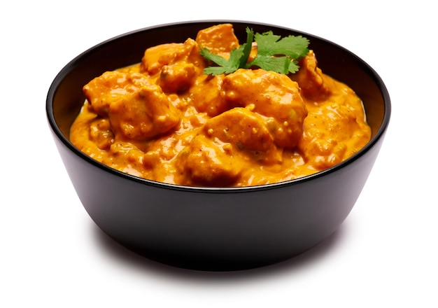 Tigela de cerâmica preta com curry de frango tradicional isolado