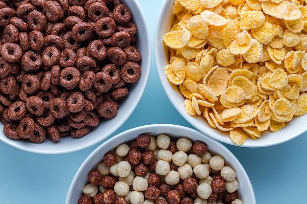 Tigela de cereais com bolas de chocolate, anéis e flocos de milho amarelo no café da manhã seco na superfície azul.