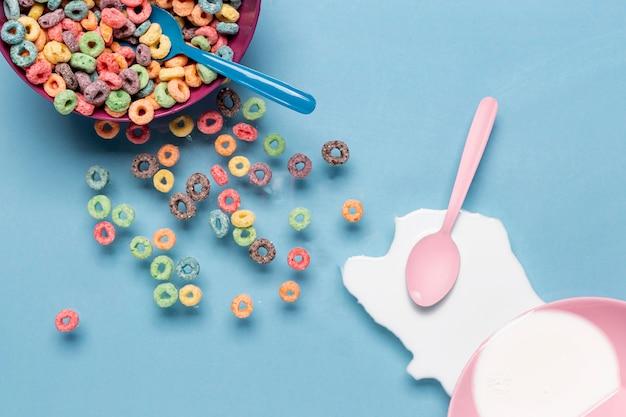 Tigela de cereais e pingo de leite com colher rosa