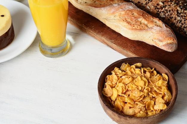 Tigela de cereais, suco de laranja e torradas