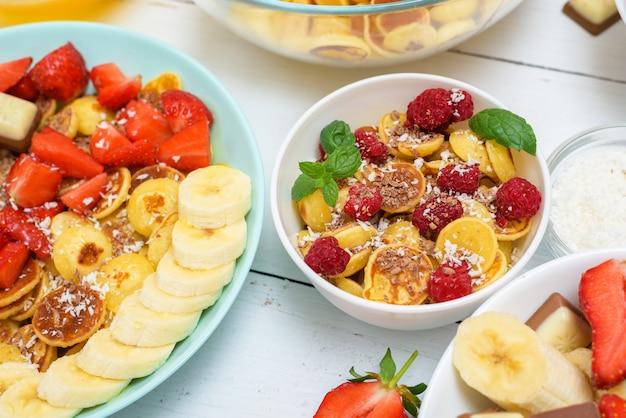 Tigela de cereal de panqueca minúscula com morangos frescos, chocolate com banana, raspas de coco e mel