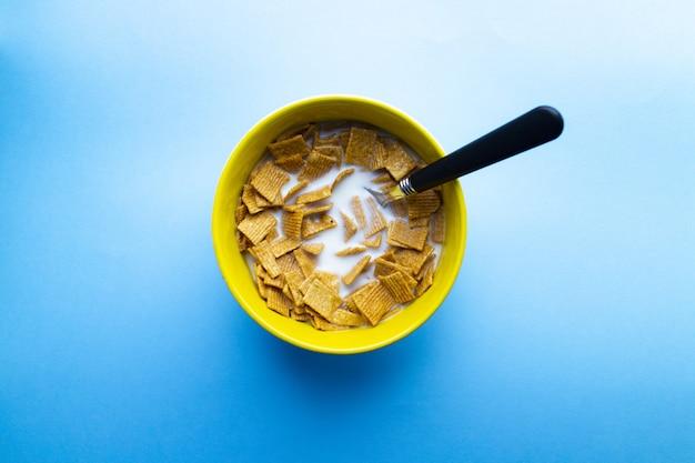 Tigela de cereal em pedaços quadrados com leite e colher em uma tigela isolada