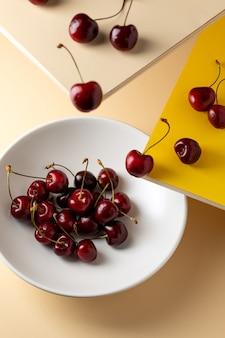 Tigela de cerejas e cerejas vermelhas frescas em superfícies de vários níveis