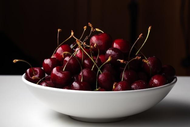 Tigela de cerejas vermelhas frescas na superfície branca