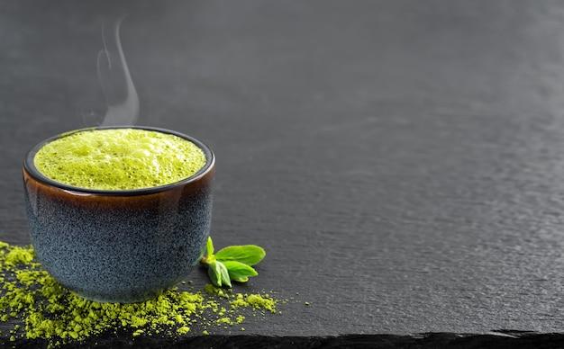 Tigela de chá azul com chá verde matcha, ao lado estão folhas de chá e chá em pó na mesa