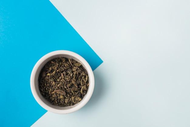 Tigela de chá seco à base de plantas em fundo azul e branco duplo