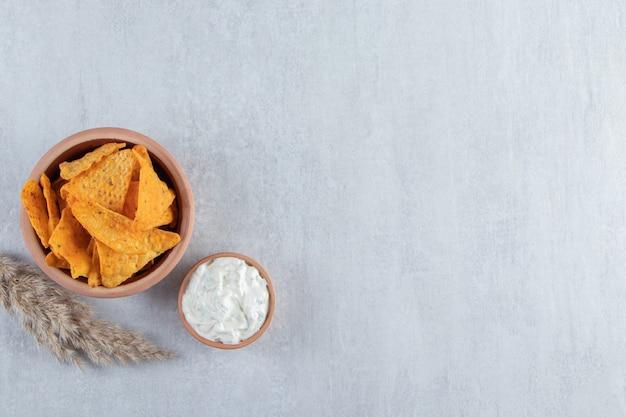 Tigela de chips de tortilha e molho especial na pedra.
