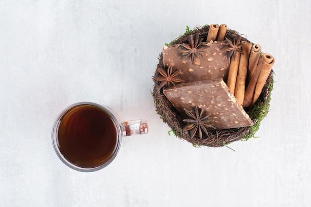 Tigela de chocolate com nozes e canela com copo de chá