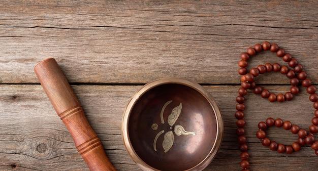 Tigela de cobre de canto tibetano com um badalo de madeira e rosário de oração em uma mesa de madeira cinza