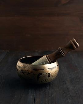 Tigela de cobre de canto tibetano com um badalo de madeira em uma mesa de madeira marrom, objetos para meditação