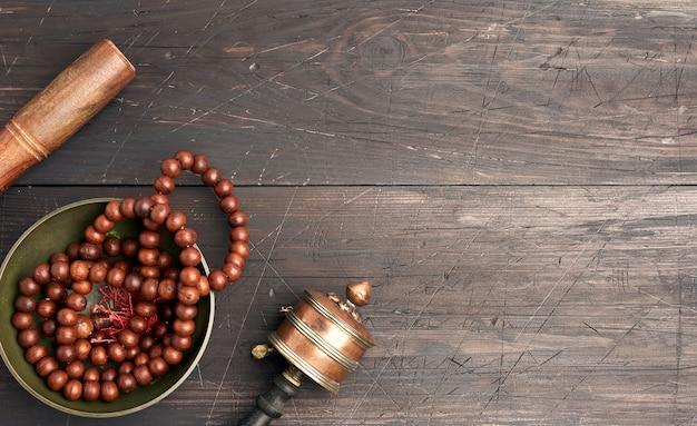 Tigela de cobre de canto tibetano com um badalo de madeira em uma mesa de madeira marrom