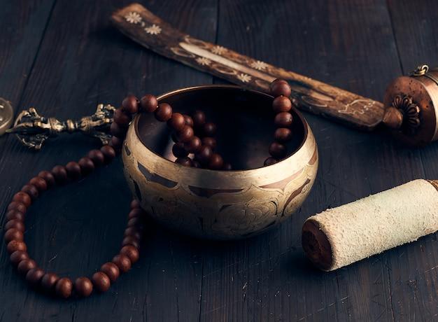 Tigela de cobre de canto tibetano com uma válvula de madeira em um marrom cortejar