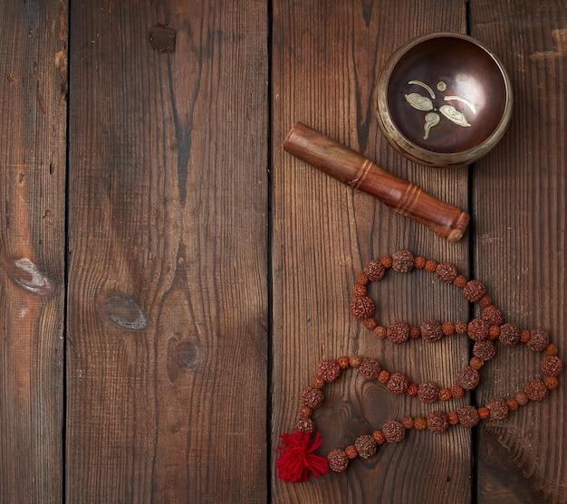Tigela de cobre tibetana e vara de madeira