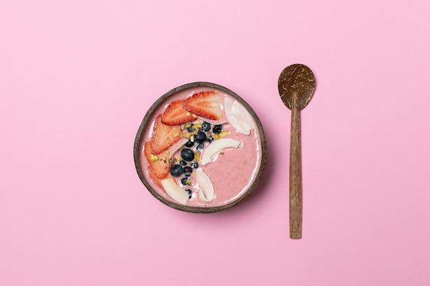 Tigela de coco com smoothie de frutas, morangos frescos, mirtilos, chips de coco