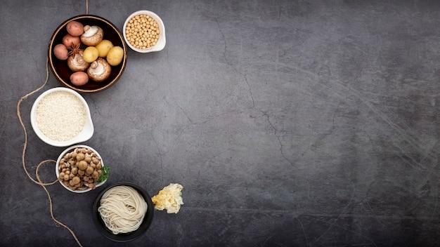 Tigela de cogumelos com tigela de macarrão em um fundo cinza