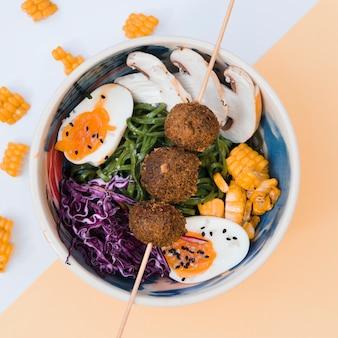 Tigela de comida asiática com ovo; macarrão; cogumelos; algas marinhas; repolho; milho e metade de ovos na tigela