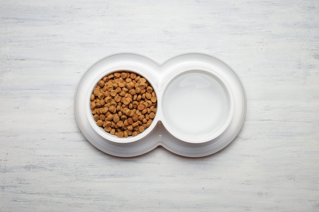 Tigela de comida de gato no fundo de madeira, vista superior