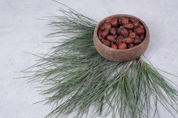 Tigela de cranberries secas e ramo de pinheiro na mesa de mármore. foto de alta qualidade