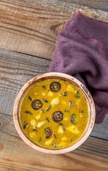 Tigela de curry de cogumelo amarelo na mesa de madeira