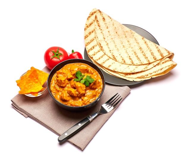Tigela de curry de frango tradicional e nachos isolados