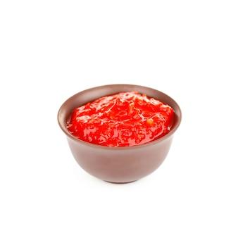 Tigela de delicioso molho de pimenta isolado no branco