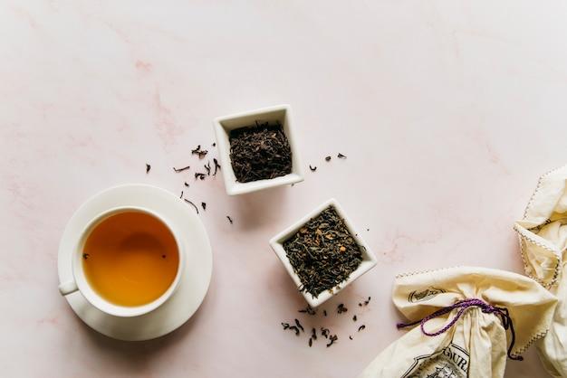 Tigela de ervas de chá secas com chá preto em pano de fundo de textura de mármore