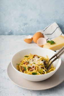 Tigela de espaguete de alto ângulo com parmesão e ovos
