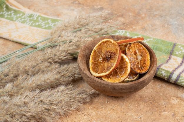 Tigela de fatias de laranja com toalha de mesa na superfície de mármore.