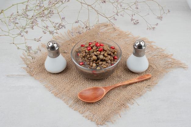 Tigela de feijão com sementes de romã e sal na serapilheira