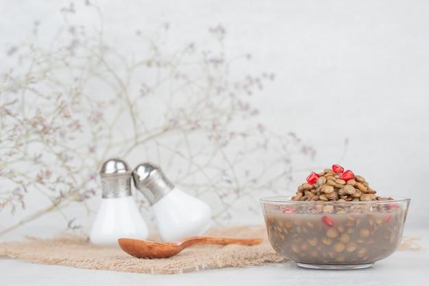 Tigela de feijão com sementes de romã na mesa branca