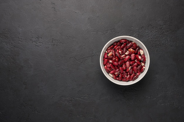 Tigela de feijão vermelho em uma superfície de madeira preta texturizada proteína vegetal comida saudável vista superior