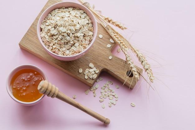 Tigela de flocos de aveia secos com mel e espigas de trigo no fundo rosa claro. cozinhar o conceito de mingau de aveia