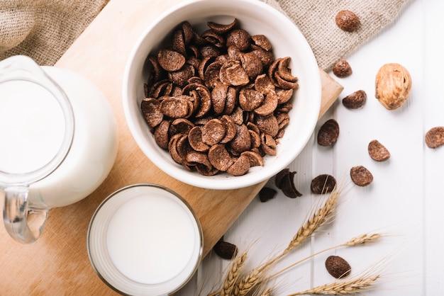 Tigela de flocos de chocolate com copo de leite na mesa