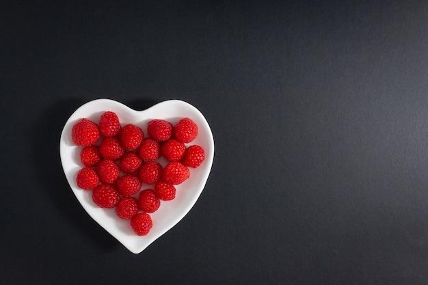 Tigela de framboesas frescas em uma tigela em forma de coração isolada na superfície preta