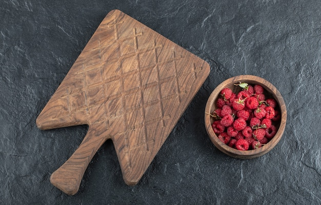Tigela de framboesas maduras com placa de madeira.