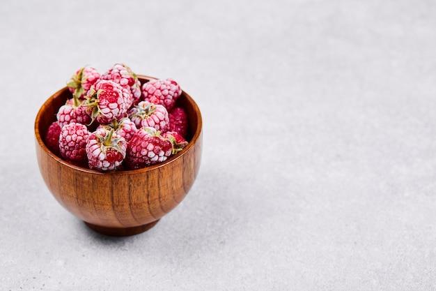 Tigela de framboesas vermelhas frescas em fundo branco.