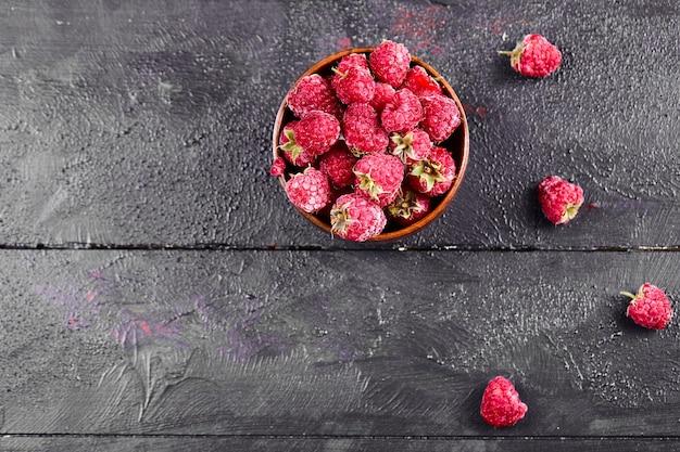 Tigela de framboesas vermelhas frescas na mesa de madeira escura.
