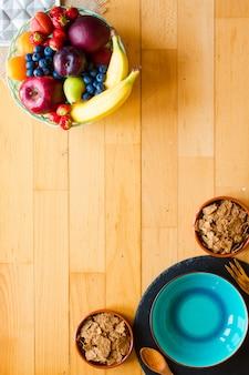 Tigela de frutas frescas com banana, maçã, morangos, damascos, mirtilos, ameixas, grãos integrais, garfos, vista superior