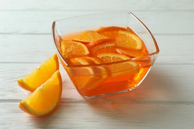 Tigela de geleia de laranja com rodelas de laranja na parede de madeira branca