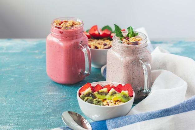 Tigela de granola caseira com iogurte e frutas frescas em fundo de madeira