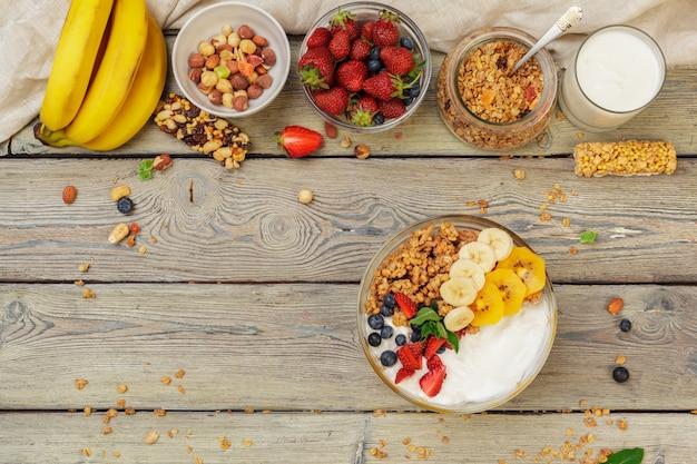 Tigela de granola caseira com iogurte e frutas frescas na madeira