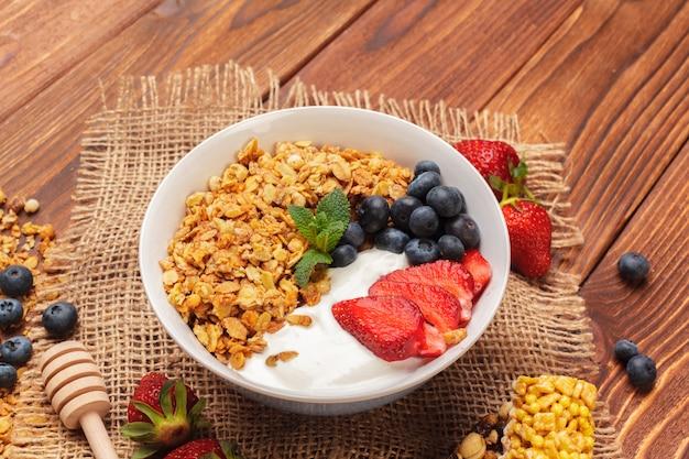 Tigela de granola caseira com iogurte e frutas frescas na superfície de madeira