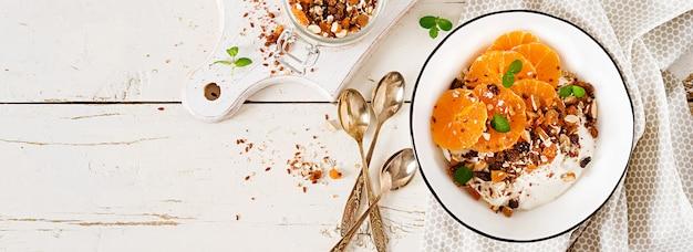 Tigela de granola caseira com iogurte e tangerina na mesa de madeira branca