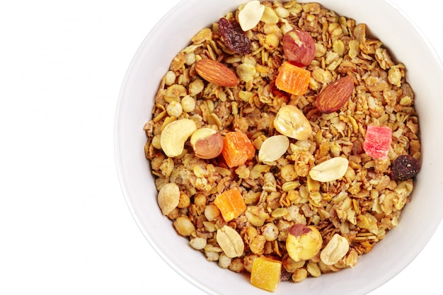 Tigela de granola caseira com pedaços de fruta isolado no branco