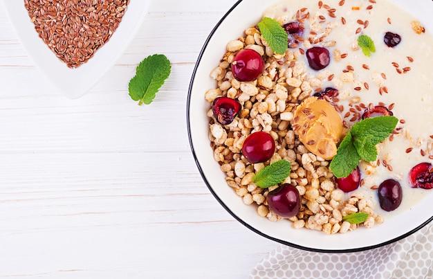Tigela de granola caseira com purê de banana, manteiga de amendoim e frutas frescas