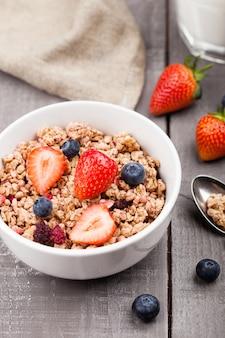 Tigela de granola de cereais saudáveis com morangos e mirtilos e copo de leite na placa de madeira