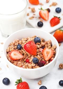 Tigela de granola de cereais saudáveis com morangos e mirtilos e copo de leite na placa de mármore