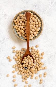 Tigela de grão de bico seco cru com uma colher, vista de cima em um pano de prato
